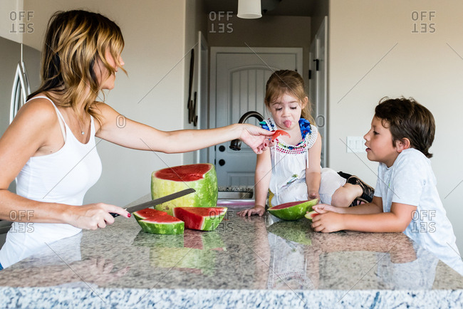 Little girl sticking out tongue as mother offers piece of watermelon as brother looks on