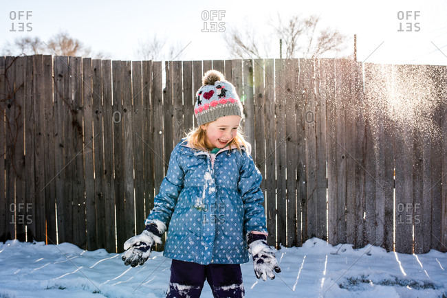 Little girl happily playing in snow on sunny winters day