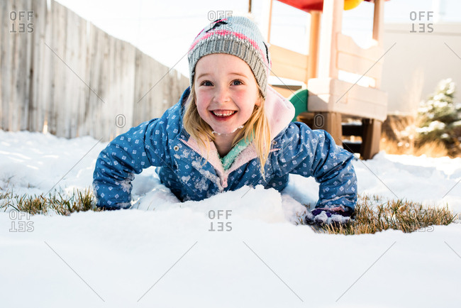 Young girl joyfully lying in fresh soft snow