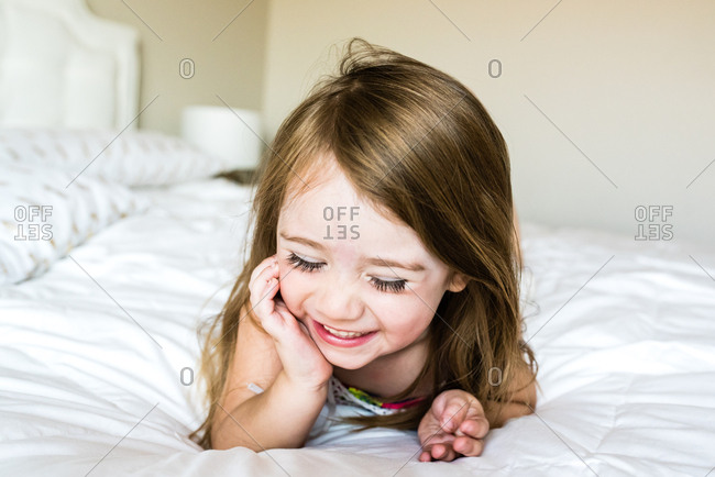 Little girl giggling while lying on bed