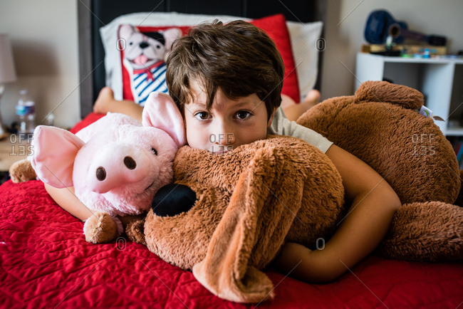 Young boy lying on bed hugging soft toys
