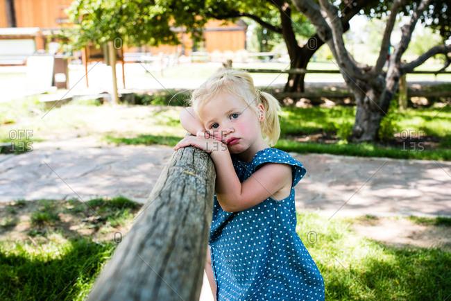 Tired little girl resting head against railing in park