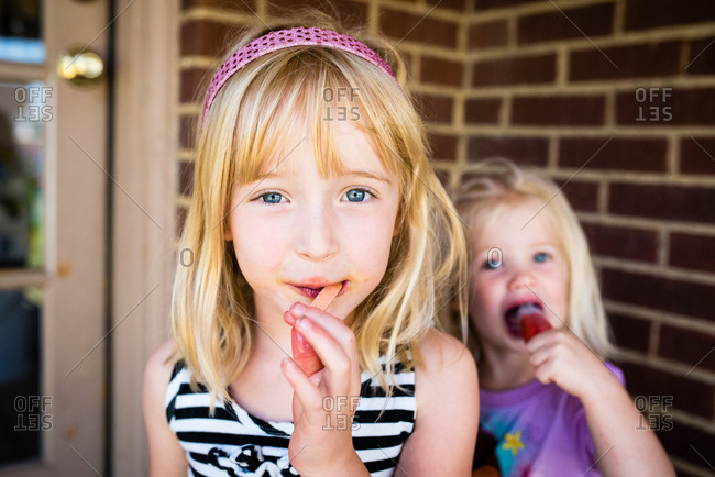Little girls all sticky and messy from eating popsicles