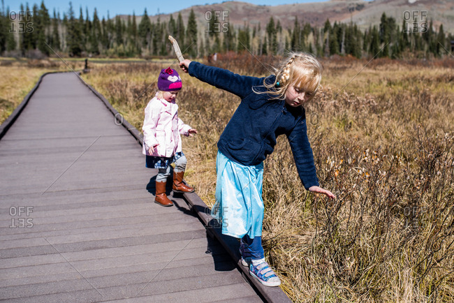 Young girl demonstrating how to balance on edge of boardwalk to little sister