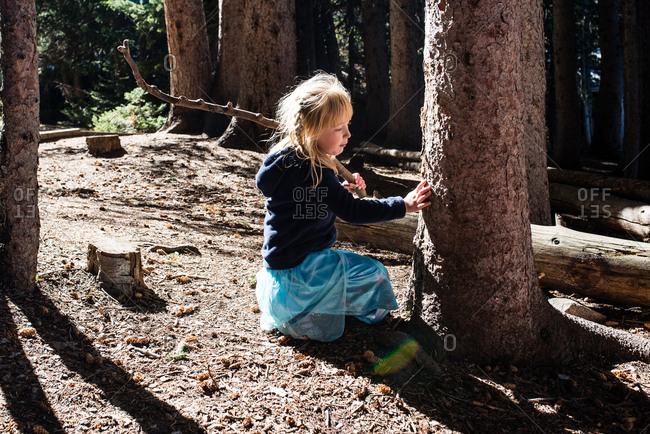 Little girl in costume kneeling exploring texture of bark of tree in forest