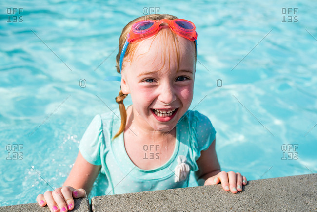 Excited little girl standing in pool smiling on hot summers day