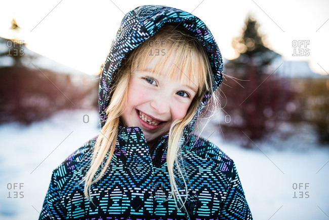 Portrait of little girl in winter coat and hood smiling mischievously