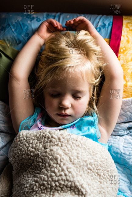 Sick little girl having a nap with arms above head