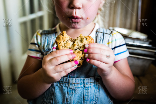 Little girls with crumbs all over her face enjoying large cookie