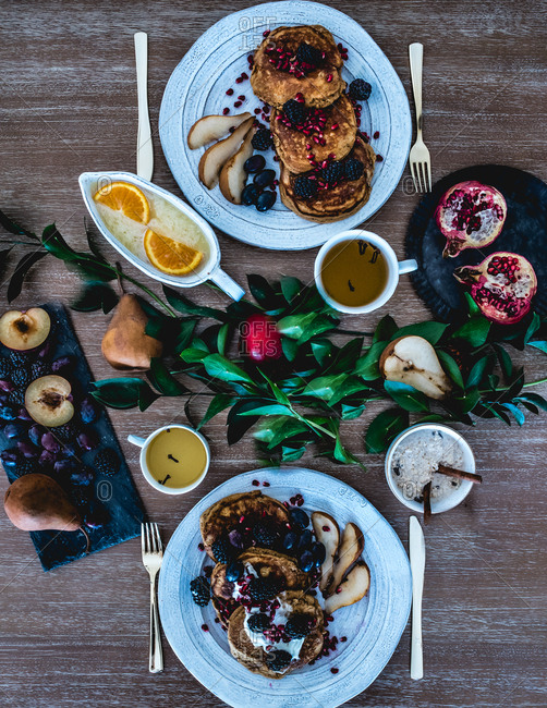 Top down view of breakfast of pancakes with berries and other fruits