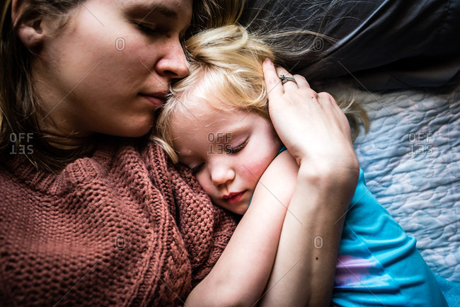 Mother hugging and comforting sick little daughter in bed