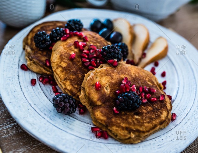 Close up view of plate of golden brown pancakes served with berries and fruit