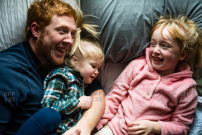 Dad goofing around and laughing with daughters lying in bed