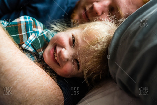 Happiest little girl in the world cuddling dad lying in bed