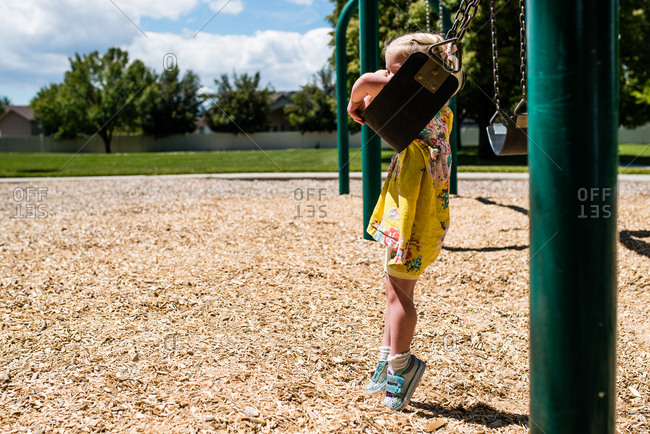 Little girl hanging onto seat of swing in park