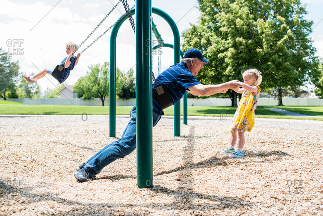 Energetic grandpa and little granddaughter playing on swings together
