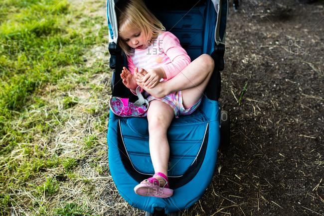 Little girl sitting in stroller checking foot