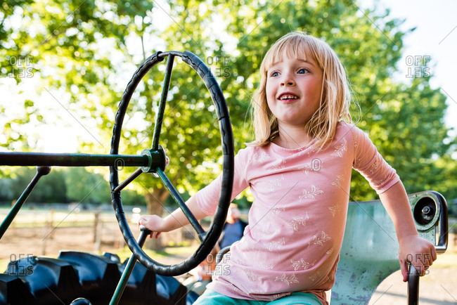Happy young girl sitting on tractor on perfect summer day