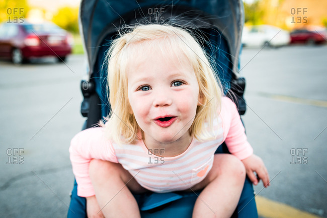 Little girl sitting in stroller in parking lot laughing