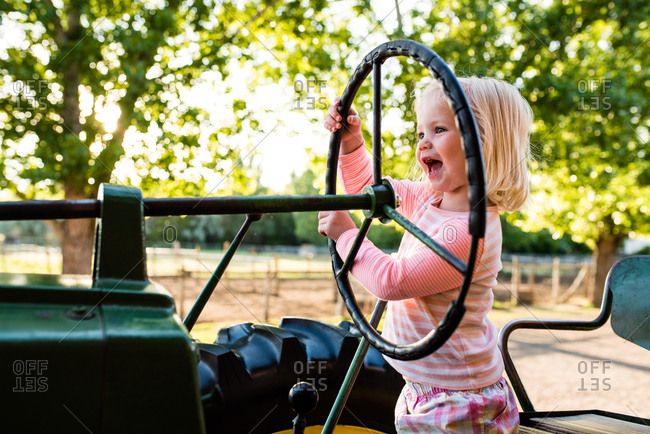 Excited little girl pretending to drive tractor