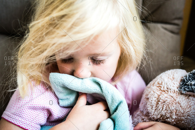 Tired out little girl sniffing comfort blanket and hugging soft toy