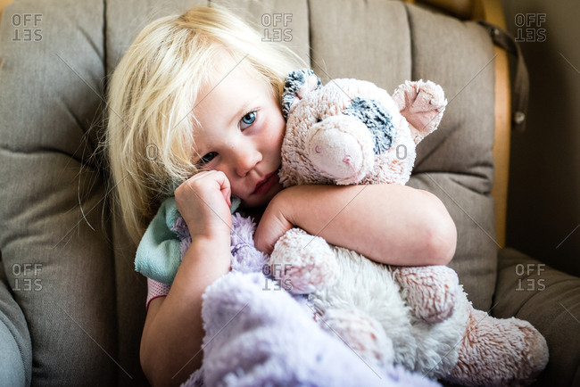 Tired little girl sitting on couch  hugging comforter and soft toy