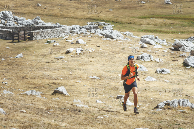 Close view of a trail runner running in the meadows close to Collado Jermoso, Leon, Spain