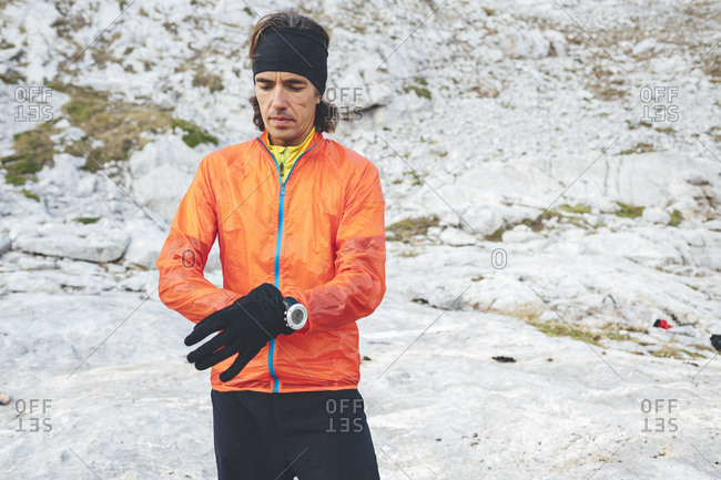 Trail runner putting on his winter gloves close to Collado Jermoso, Leon, Spain
