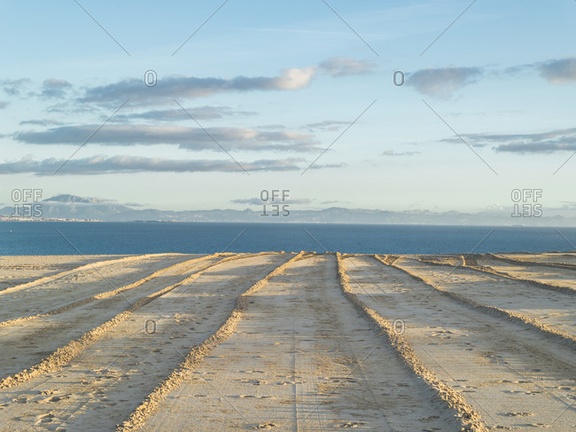 Lanes made in the sand of  Punta Paloma sand dune and Gibraltar Strait at sunset, Cadiz, Spain