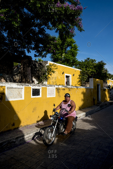 Izamal, Mexico - October 14, 2017: Large man on small motorbike riding by weathered yellow wall