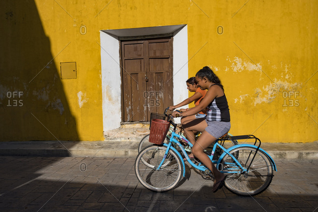 Izamal, Mexico - October 14, 2017: Women pedaling past a weathered yellow wall