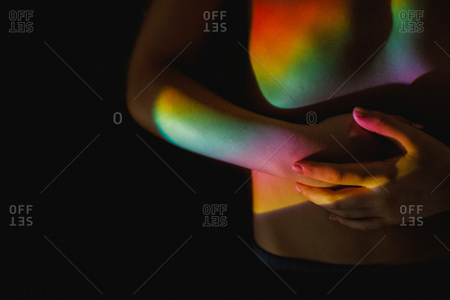 Rainbow hued light falling across naked torso of person