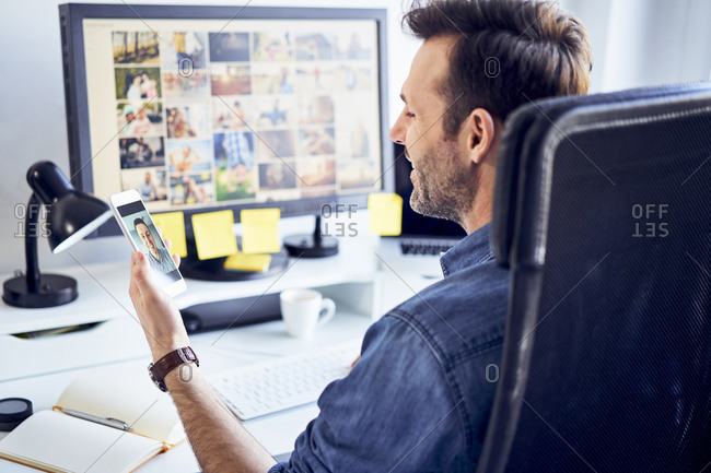 Photo editor at desk in office having video chat on his phone