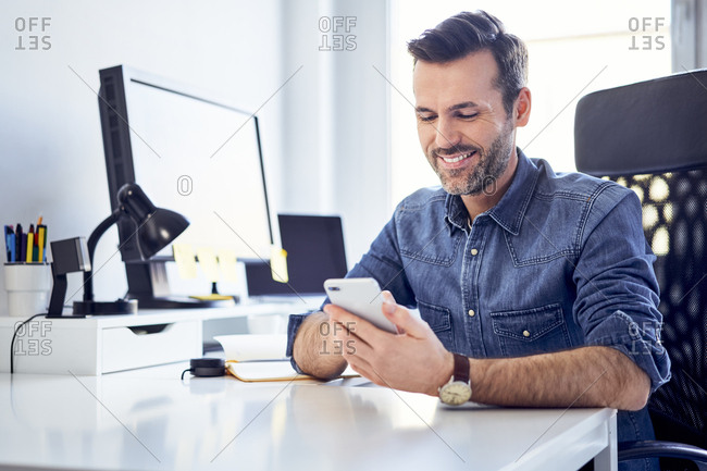 Smiling man using cell phone at desk in office