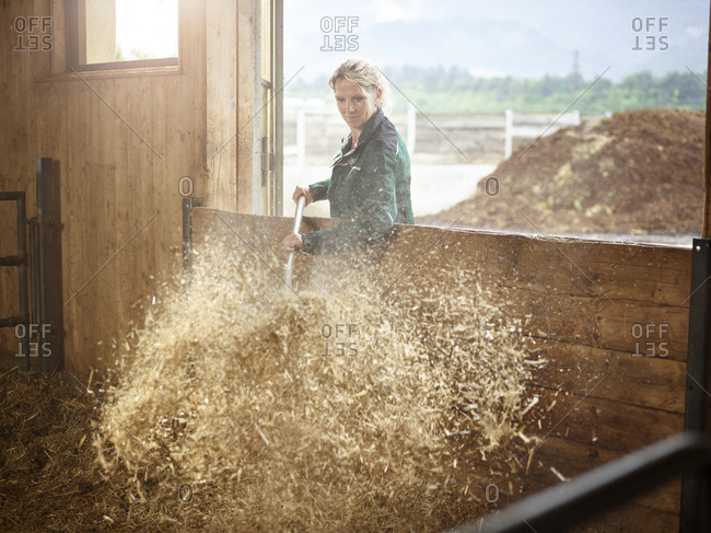 Female farmer working with straw on a farm