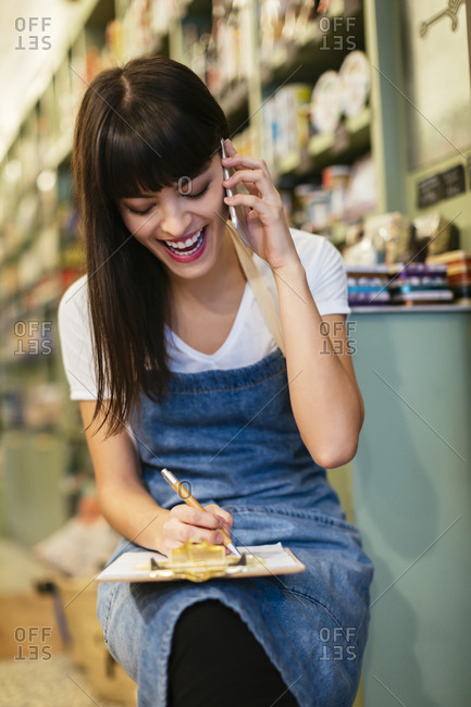Laughing woman on the phone in a store taking notes