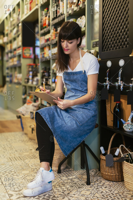 Woman sitting on stool in a store taking notes