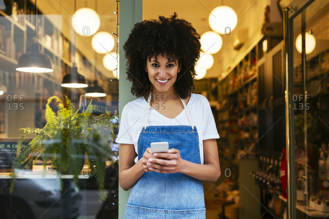 Portrait of smiling woman with cell phone standing in entrance door of a store