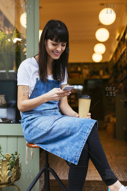 Smiling woman sitting on stool using cell phone at entrance door of a store