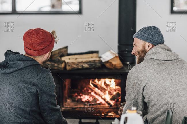 Two men sitting at fireplace