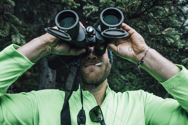 Man smoking a cigarette looking through binoculars in nature