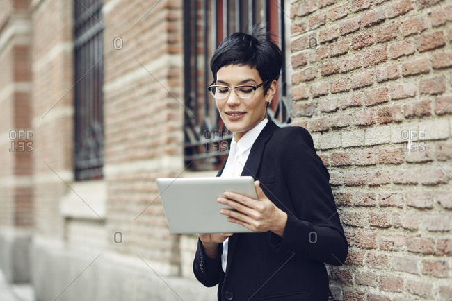 Portrait of content young businesswoman using tablet outdoors
