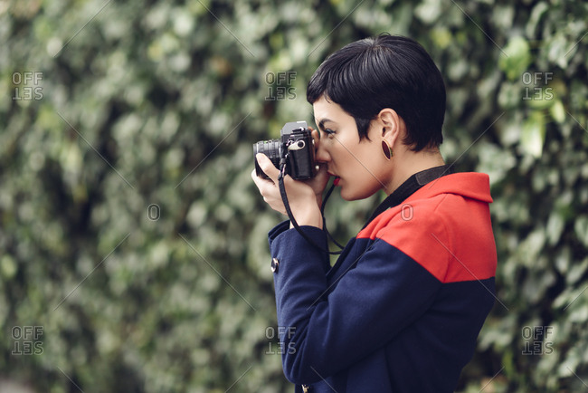 Fashionable young woman taking photo with camera