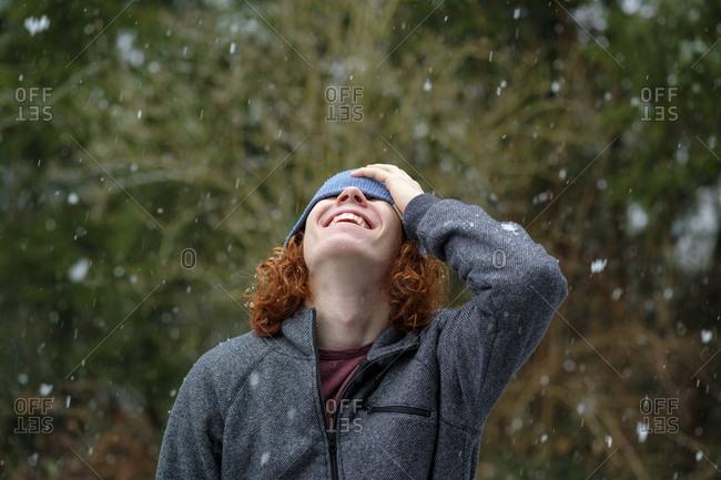 Happy teenage boy enjoying snowfall