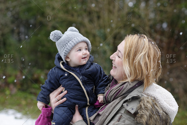 Baby girl on arms of her mother watching snowflakes for the first time