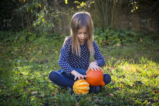 Little girl sitting on meadow in autumn playing with pumpkins