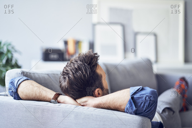 Relaxed man lying on sofa
