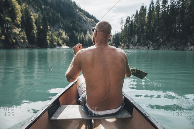 Canada- British Columbia- barechested man in canoe on Kinbasket Lake