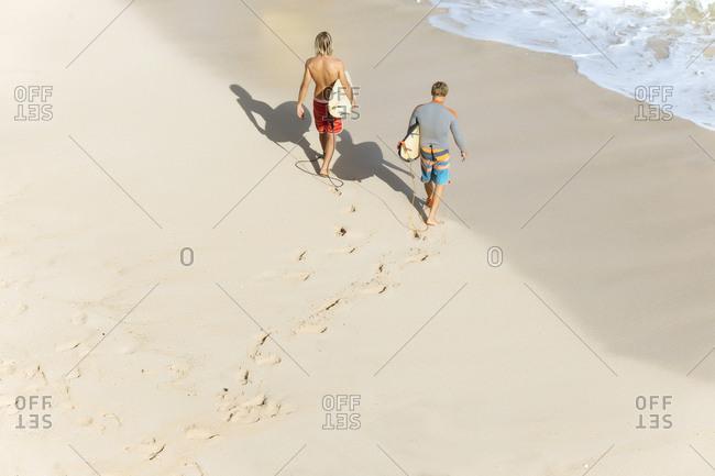 Indonesia- Bali- Surfers walking aat Bingin beach