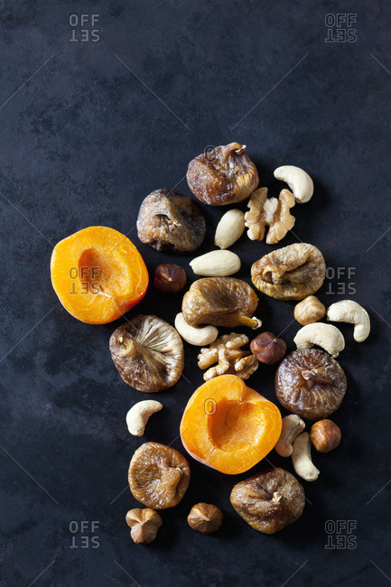 Sliced apricot- dried figs- almonds and various nuts on dark ground